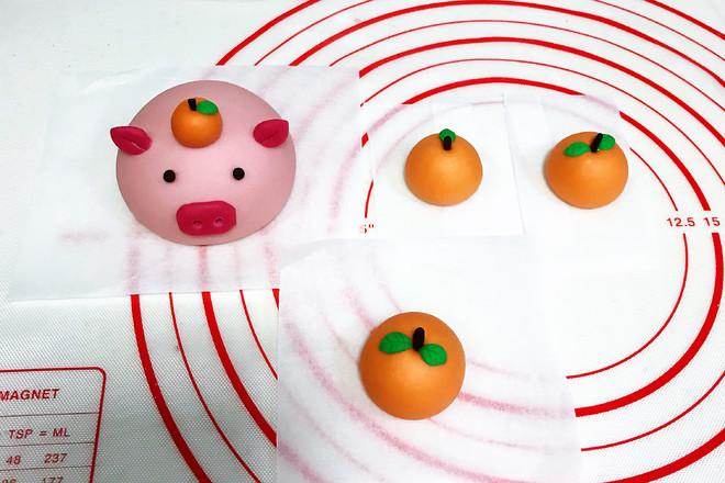 把橘子蒂插入孔中,绿色的叶子也粘上,然后取一点点搓圆做小猪的眼睛.